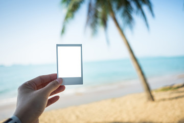 hand of woman holding blank postcard on beach with sea and coconut tree background