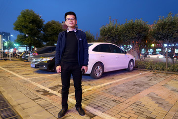 Ruan Pengfei poses for a photo near his car in Pingdingshan