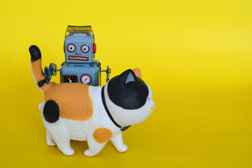 Vintage tin toy robot and a cat isolated on a yellow background.