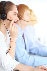 Call center operators at work. Focus at  business woman in headset