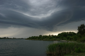 Dramatic landscape with storm clouds over the lake.