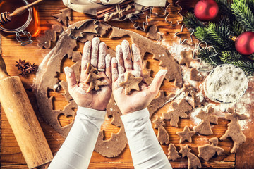 Christmas baking and gingerbread star and tree in woman hands