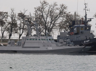 Seized Ukrainian ships, small armoured artillery ships and a tug boat, are seen anchored in a port of Kerch