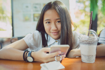 close up face asian teenager happiness smiling face with smart phone in hand