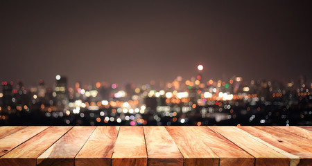Empty of white wood table top on blur night town,cityscape backgrounds.For montage product display or key visual
