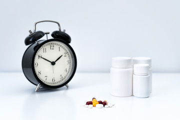 Alarm clock tablet capsules and a glass of water