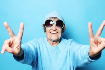 Funny old lady wearing blue sweater, hat and sunglasses showing victory sign