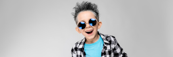 A handsome boy in a plaid shirt, blue shirt and jeans stands on a gray background. The boy is wearing round glasses. The boy is smiling. The boy has an ashy hair color