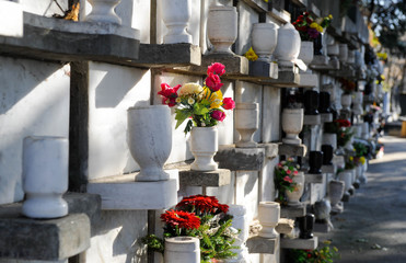 Urns with ashes in a columbarium wall of the cemetery