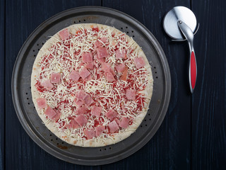 Frozen pizza with ham on a rusty tray, on a dark background
