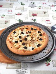 Freshly baked pizza with porcini and truffle, on a rusty tray, with pizza cutter aside