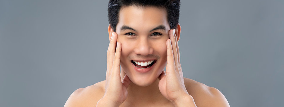 Portrait of handsome smiling young Asian man with hands touching face