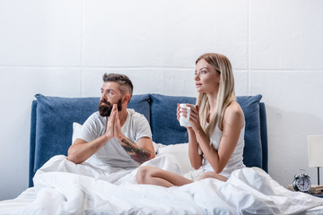 Young couple drinking coffee in white bed in morning