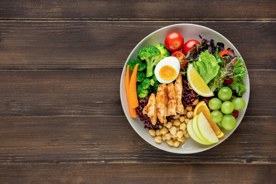 Clean food with mixed vegetable and fruit salad on wood table background