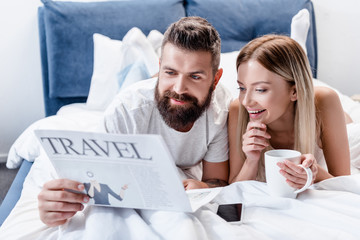 bearded man and young woman with coffee cup lying in bed and reading travel newspaper
