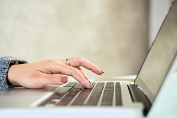 Close-up of female hands typing on computer keyboard at the table