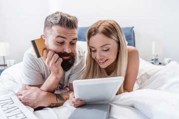 Smiling couple lying in bed and doing online shopping