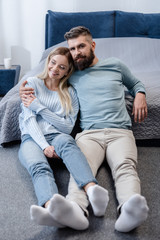 Handsome man sitting on floor and embracing attractive young girl in blue bedroom