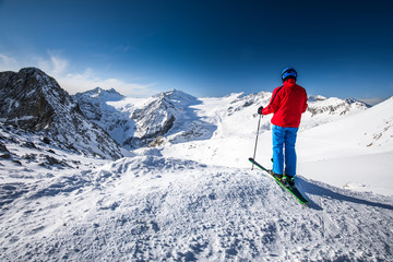 Young happy attractive skier on the top of mountains enjoying the view from Presena Glacier, Tonale, Italy