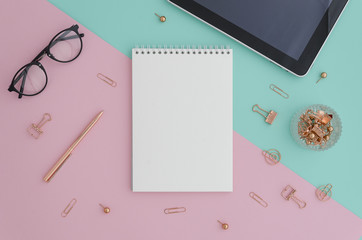 Creative flat lay photo of workspace desk with tablet, eyeglasses, gold accessories and notebook with copy space vibrant duotone background, minimal style. Flat lay blog mock-up