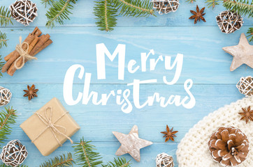Merry Christmas greeting card with handwriting lettering on rustic blue wooden background christmas tree, cinnamone,anice star, pine cones and fir tree. Winter holiday seasonal greetings card. Xmas.