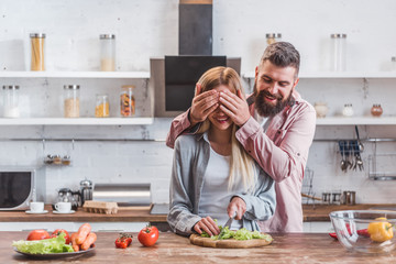 Husband smiling and closing eyes of wife in kitchen