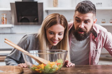 surprised cheerful couple looking at salad in glass bowl at kitchen table