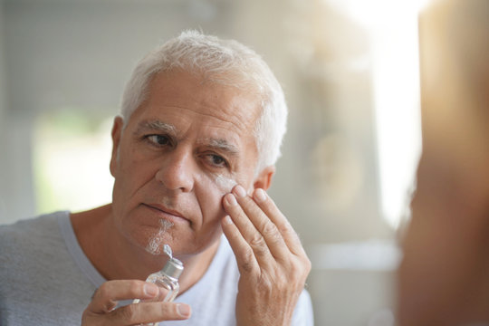 mature man in front of mirror using cosmetics