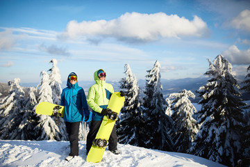 Two snowboarders posing at ski resort. Riders friends carrying their snowboards through forest for backcountry freeride and wearing reflective goggles, colorful fashion outfit. Copyspace area.