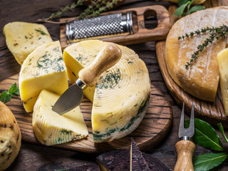 Cheese wheel with herbs and cutlery on the wooden background.