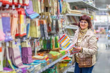 Beautiful mature woman chooses textile store.