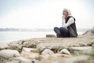 Beautiful elderly woman sitting by the ocean in sportswear