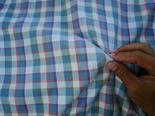 Women hand with Square pattern fabric background. Scott chintz fabric for design.Plaid cotton texture.