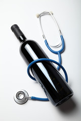 Glass bottle of red wine and stethoscope. Prevention of heart disease.