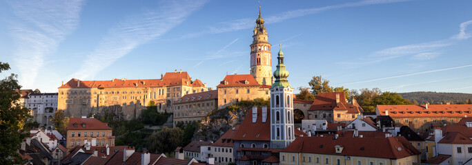 Panoramic view of the State Castle and Chateau Cesky Krumlov, tower of St. Jost church and historic red roof houses in Cesky Krumlov, Czech Republic, during morning sunrise