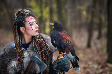 Outdoor portrait of Viking warrior woman princess in woods wearing fur collar, braided hair and specific makeup with face covered in blood holding hawk in hand. Northern woman with bird of prey