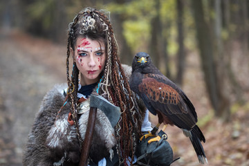 Beautiful Viking warrior woman in woods wearing fur collar, braided hair and specific makeup with face covered in blood holding hawk in hand. Northern woman with her predator in forest Fotoväggar