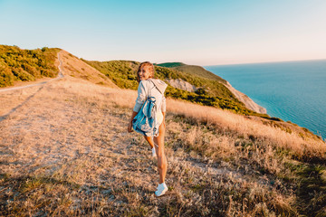 Attractive smiled woman outdoor at warm sunset. Happy holiday in the mountains