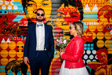 Couple of newlyweds pose in front of a graffitied metal blind