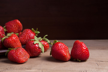 Strawberry fresh ripe sweet berry in clay plate on wooden background.