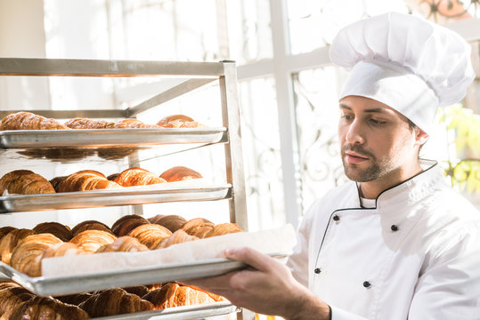 baker in chefs uniform looking at trays with fresh cooked croissants