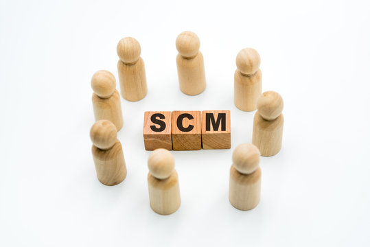 Wooden figures as business team in circle around acronym SCM Supply Chain Management
