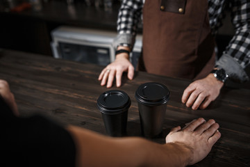 The buyer buys coffee at a bar in a modern cafe. Close-up
