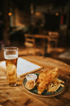 Fish and chips plate and pint of beer on a wooden table at the pub.