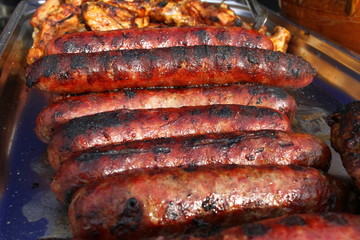 Grilled smoked sausages and meatballs outdoors. Meat baked on the grill bbq. Meat delicacies. Sausages homemade sausages on the grill. Street food. Festival of street food.