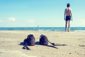 Black sneakers on the sand on the sea and boy background. Summer and travel concept