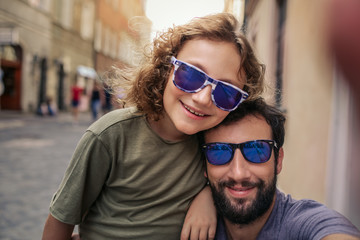 Smiling boy and his father taking selfies outside