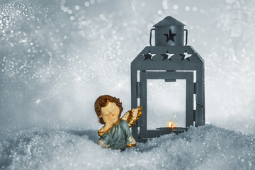 Christmas angel and a lantern with a candle on a snow on a sparkling silver background