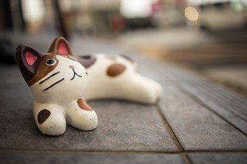 Cute brown and white cat figure lounging lazily on the ground outside
