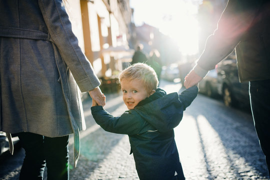 A rear view of small toddler boy with unrecognizable parents walking outdoors in city.